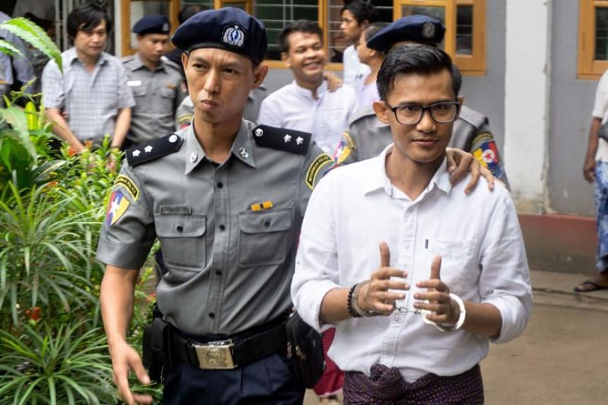Detained Myanmar journalist Kyaw Zaw Lin leaving the courthouse escorted by police after appearing before the Tamwe township court, on Oct 10, 2018.