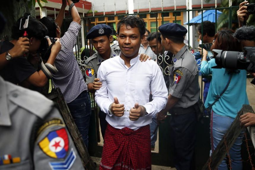Chief reporter of Eleven media Phyo Wai Win, gestures in handcuffs as he leaves Tamwe township courts on Oct 10, 2018.