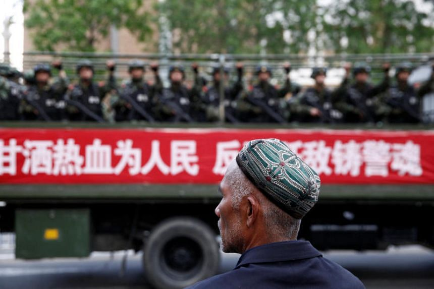 """An Uighur man looks on at an anti-terrorism oath-taking rally in Urumqi, Xinjiang. Rules were introduced to standardise controversial anti-terror """"re-education centres"""" on Oct 9, 2018."""