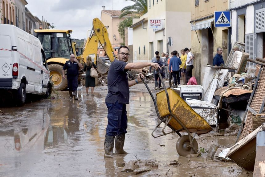 Residents work to clean a street after flash floods hit the village of Sant Llorenc des Cardasar.