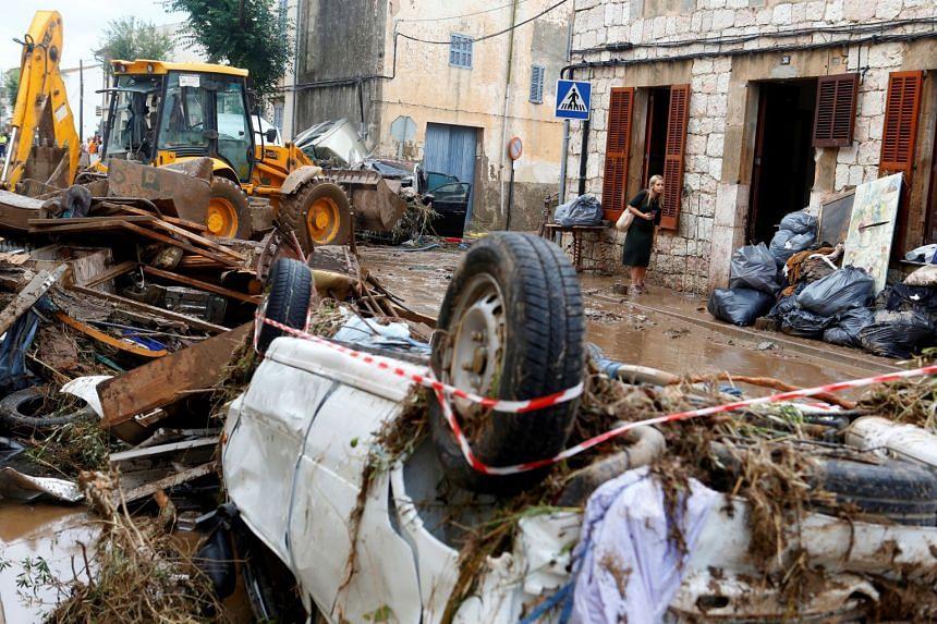 A resident walks through debris as heavy rain and flash floods hit Sant Llorenc de Cardassar on the island of Mallorca.