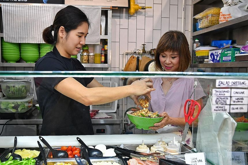 Ms Poh Ying Min (left), who runs a customised salad bowl stall at Block 163 Bukit Merah Central Food Centre under the Incubation Stall Programme, making a bowl of salad for Senior Minister of State for the Environment and Water Resources Amy Khor yes