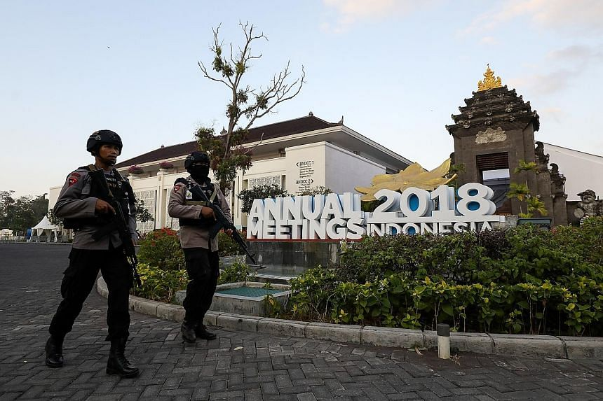 Police officers patrolling outside the venue of the International Monetary Fund-World Bank annual meetings in Nusa Dua, Bali, yesterday. While evidence of the impact of a trade war on economic momentum is, as yet, hard to detect, trade frictions rema