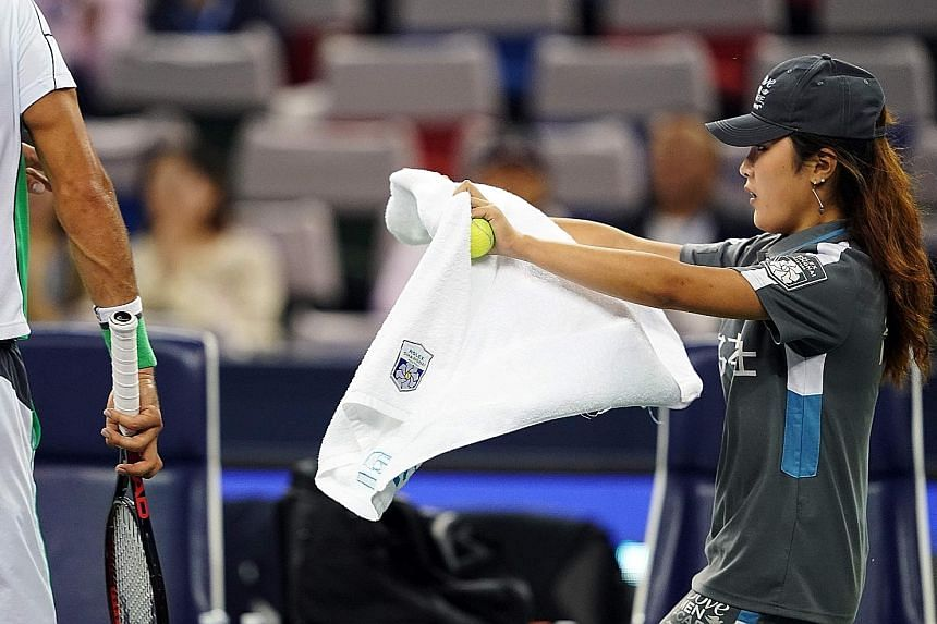 The behaviour of tennis pros towards ball kids such as this girl has come under scrutiny following Fernando Verdasco's rant over a towel at the Shenzhen Open.