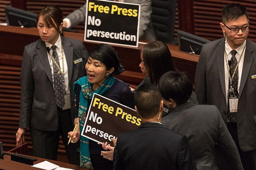 Pro-democracy lawmaker Claudia Mo being escorted out of the legislative chamber as she shouted slogans supporting press freedom. Chief Executive Carrie Lam has warned against splitting the city from China.