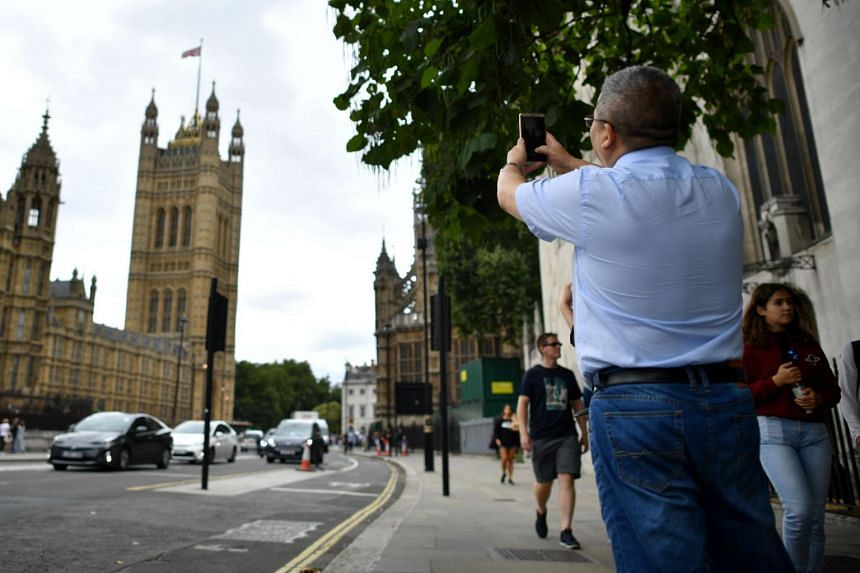 A tourist taking a photograph of the Houses of Parliament in central London, on Aug 15, 2018.