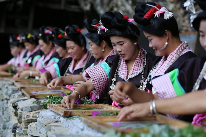 Women of the Miao ethnic minority making floral decorations to celebrate the traditional Chixin festival in Danzhai county, Guizhou province.