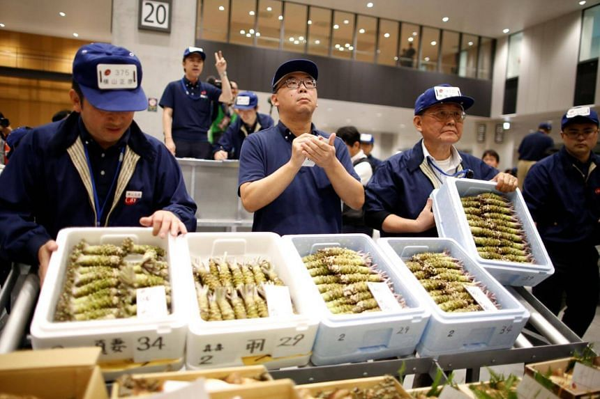 Auctioneers take part in a wasabi auction on the opening day of the new Toyosu market in Tokyo, on Oct 11, 2018.