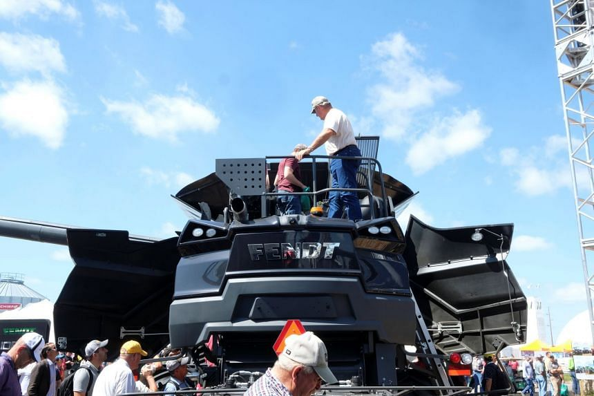 People inspect a farming vehicle at an agricultural trade show in Iowa on Aug 29, 2018. Farmers in the US state have been cautious about spending money on new equipment.