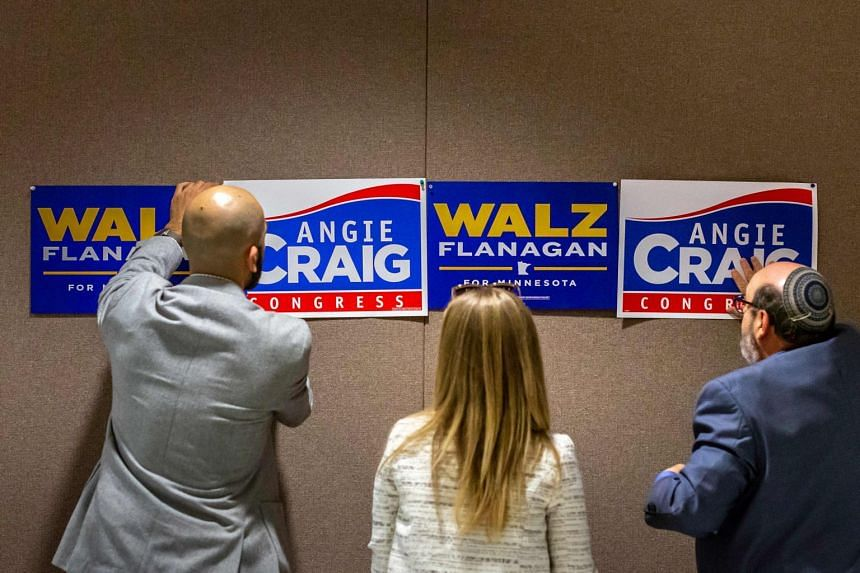 """Staff for Democrat Angie Craig hang posters at a campaign event in Minnesota on Oct 4, 2018. A much heralded Democratic """"blue wave"""" could crest - or peter out - in next month's US midterms."""