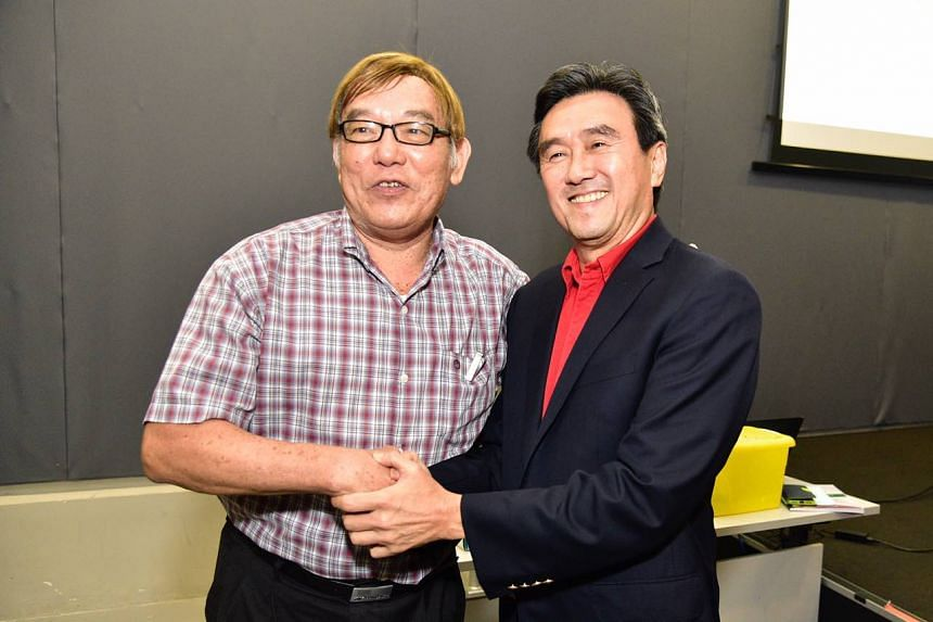 Current Singapore Athletics president Ho Mun Cheong (left) shaking hands with newly minted SA president Tang Weng Fei after a biennial election on Oct 11, 2018.