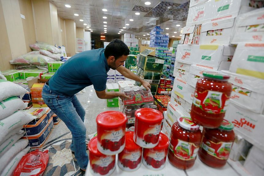 A worker arranges cans of Iranian tomato paste at a supermarket in Najaf, Iraq on Oct 7, 2018.
