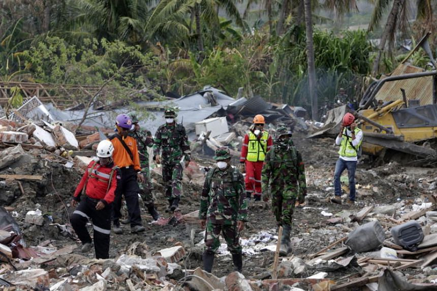 Rescue teams use an excavator to search for a body in the ruins of a house at Balaroa village in Palu on Oct 11, 2018.