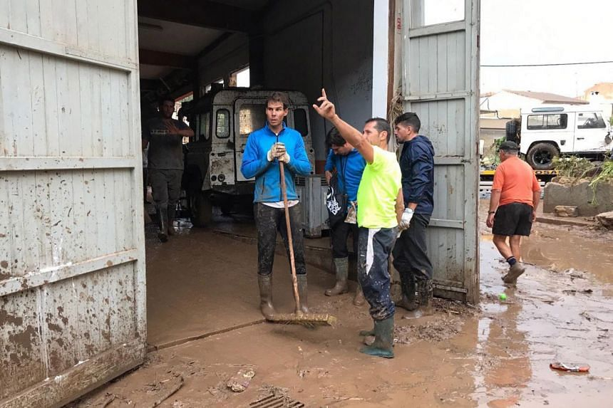 Nadal (left) takes part in cleaning works a day after flash floods hit Mallorca.