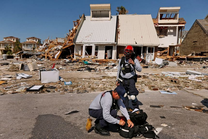 Members of search and rescue crew are seen next to property damaged by Hurricane Michael in Mexico Beach, Florida.