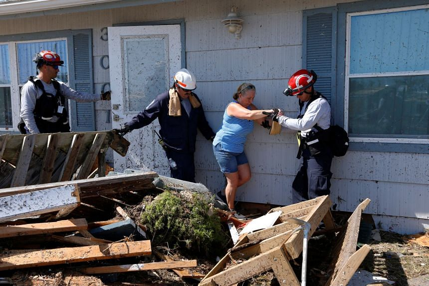 Bianna Kelsay is rescued from a building damaged by Hurricane Michael in Mexico Beach, Florida.
