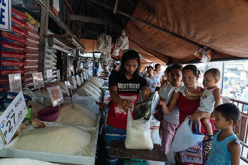 People queuing for subsidised rice in Manila last month, where soaring food prices are a source of widespread discontent.