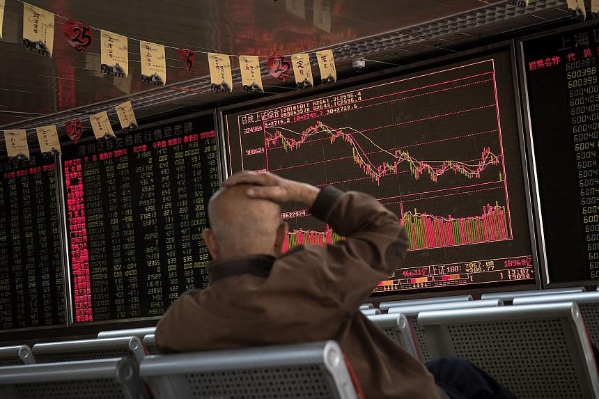 A man watching an electronic board showing the stock index and prices at a securities brokerage in Beijing yesterday. Stock markets across Asia plunged after the Dow Jones fell more than 800 points.