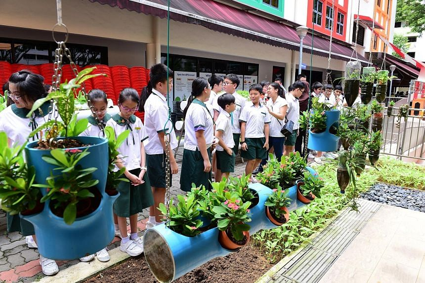 Zhenghua Primary School pupils on an experiential learning trail at the Bukit Panjang CC yesterday, where they learnt about community gardening and how it contributes to the sustainable production of food.
