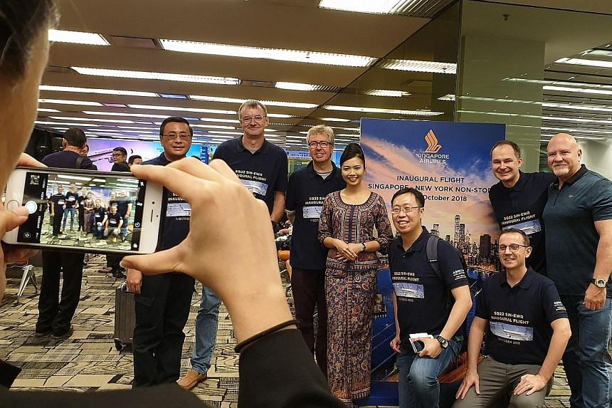 Aviation enthusiasts, clad in T-shirts made to commemorate Singapore Airlines' launch of the world's longest non-stop commercial service, at yesterday's pre-flight reception in the gatehold room.