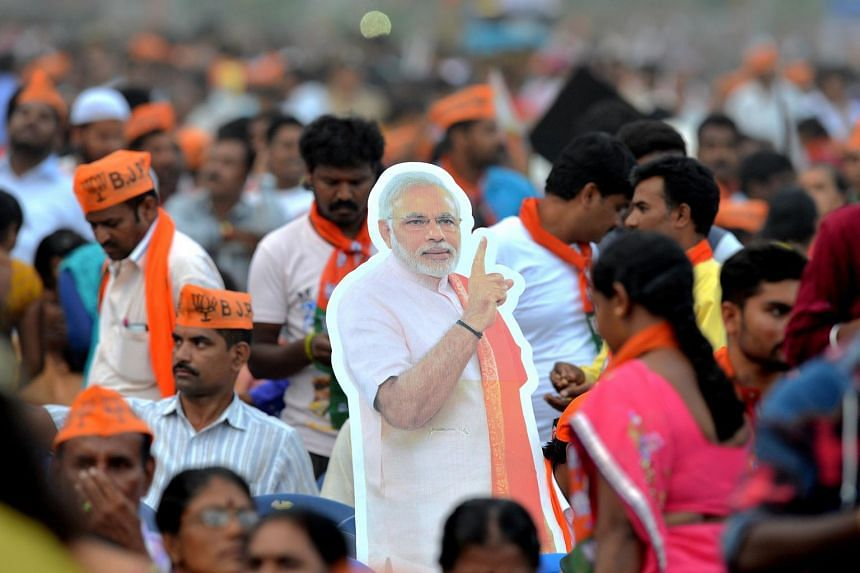 Supporters hold up a cutout of Indian prime minister Narendra Modi at a rally in Bangalore on May 3, 2018. The Bharatiya Janata Party is betting big on Modi's charisma in upcoming national elections.