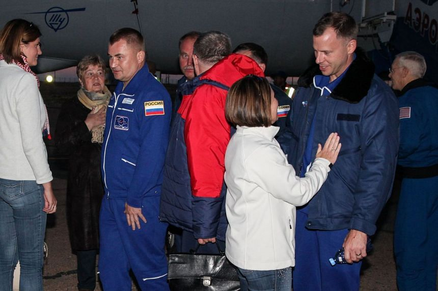 NASA astronaut Nick Hague and Russian cosmonaut Alexey Ovchinin are welcomed by family members and officials.