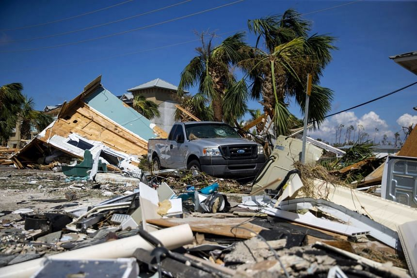A damaged pickup truck is surrounded by wreckage and debris in Mexico Beach Florida