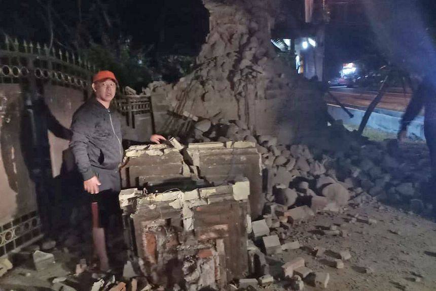 A photo provided by the Indonesian disaster management agency showing a man at a damaged building in Sumenep regency, East Java, yesterday. The epicentre of the quake was 55km north-east of East Java.