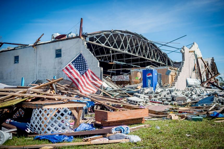 A US flag waves outside the collapsed 15th Street Flea Market in Panama City, Florida.