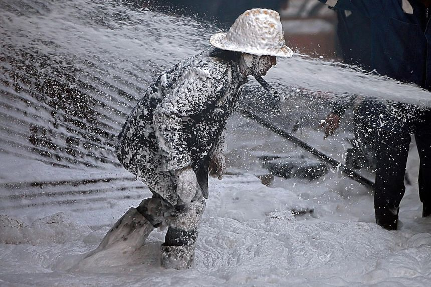 A firefighter covered with aqueous film-forming foam, a type of firefighting foam, amid efforts to control a blaze that broke out in a thinner manufacturing plant on the outskirts of Ahmedabad in the western state of Gujarat, India, on Thursday. A vi