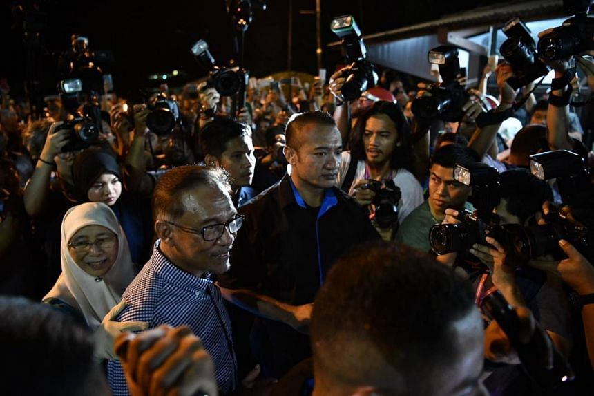 Datuk Seri Anwar Ibrahim, accompanied by his wife Wan Azizah, departing the counting centre after the announcement of voting results in Port Dickson, on Oct 13, 2018.