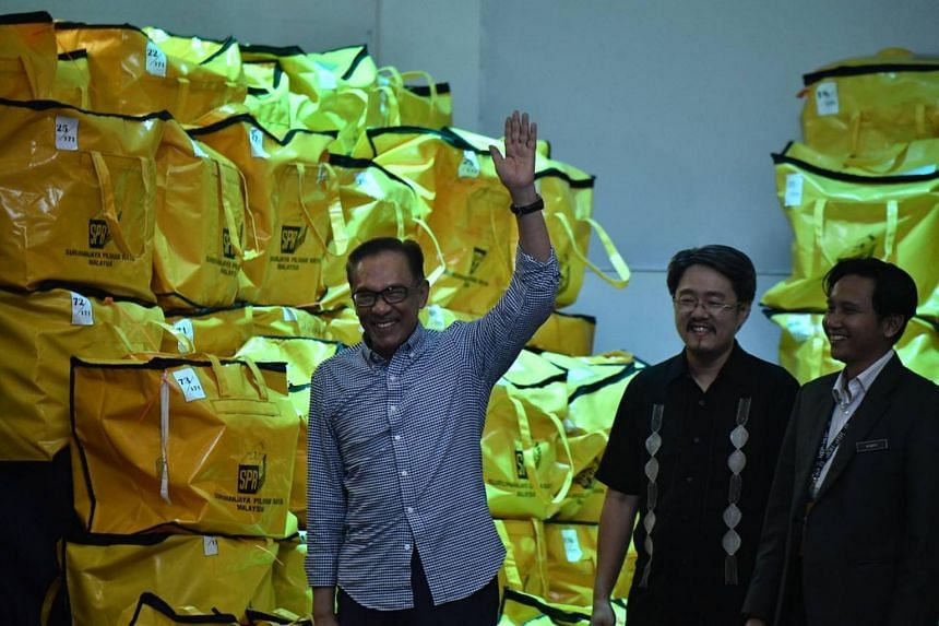 Datuk Seri Anwar Ibrahim gestures to supporters at the counting centre after the announcement of voting results in Port Dickson, on Oct 13, 2018.