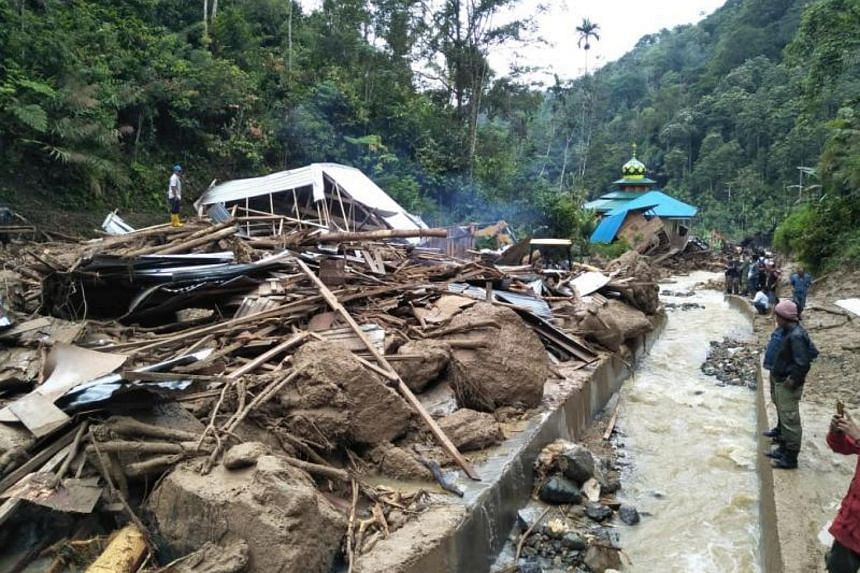 Villagers examine a site after it was hit by flash floods at the Saladi village in Mandailing Natal, North Sumatra on Oct 13, 2018.