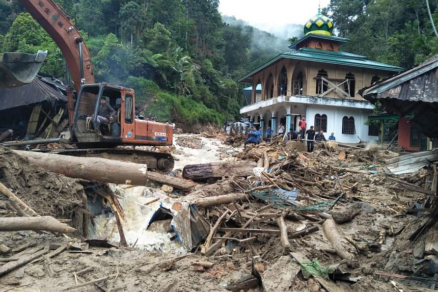 Heavy equipment is used to remove debris after flash floods hit the Saladi village in Mandailing Natal, North Sumatra on Oct 13, 2018