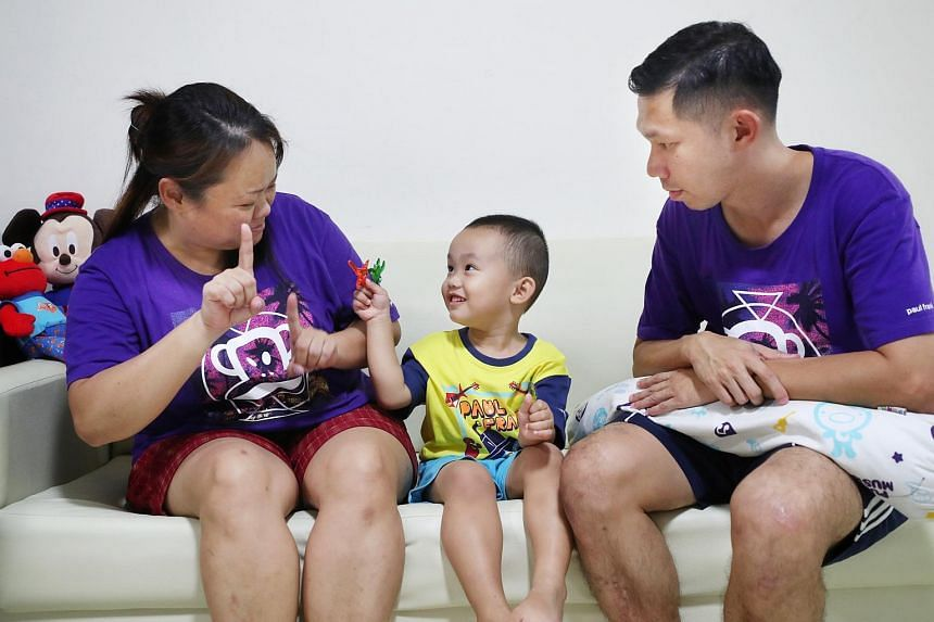 """Ms Phoebe Heng (left), 39, teaches her son Micah Chan, three, how to sign """"star fish"""". Ms Heng and her husband Moses Chan, 39, are deaf, while their son has no hearing disability."""