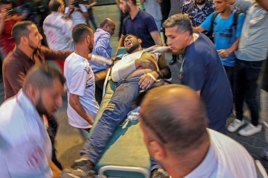 Palestinian men carry an injured protester into a hospital in Gaza City.
