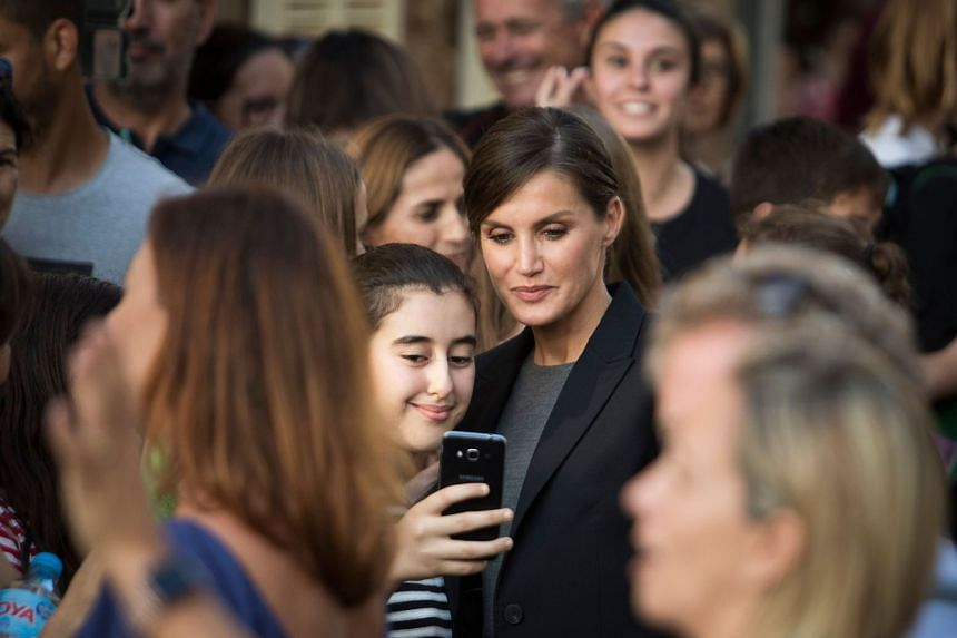 Queen Letizia (centre) poses for a picture with a young girl during her visit to Llorenc des Cardassar.