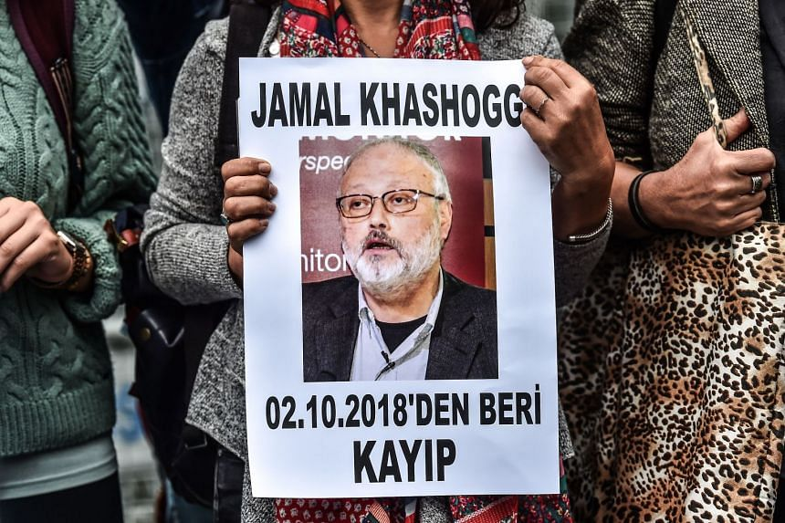 """A woman holds a portrait of Khashoggi reading """"Jamal Khashoggi is missing since Oct 2"""" during a protest at the Saudi Arabian consulate in Istanbul."""