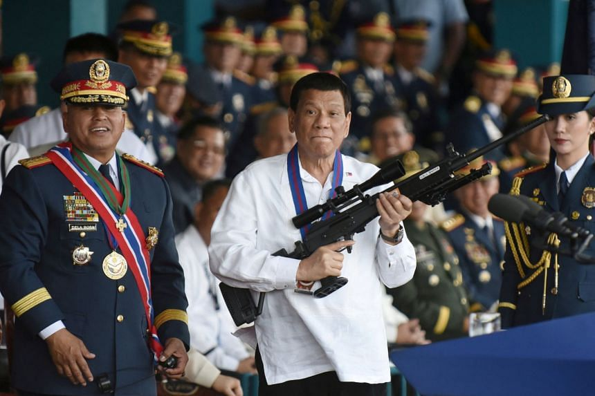 Mr Duterte holding a Galil sniper rifle at a national police chief handover ceremony in April 2018.
