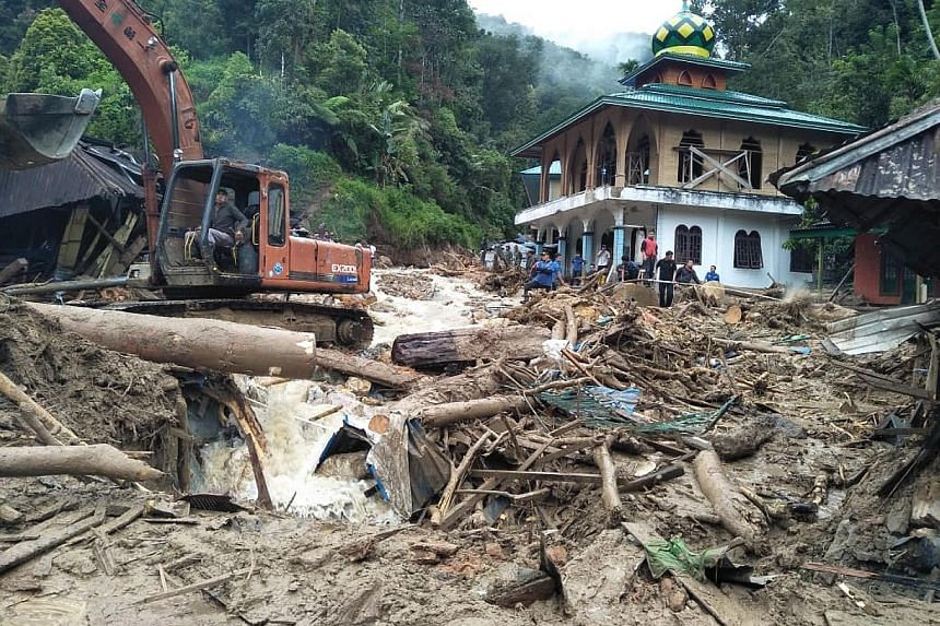 Rescue workers removing debris after flash floods hit Muara Saladi village in Mandailing Natal yesterday. Eleven students died after being swept away when a landslide smashed into their school.