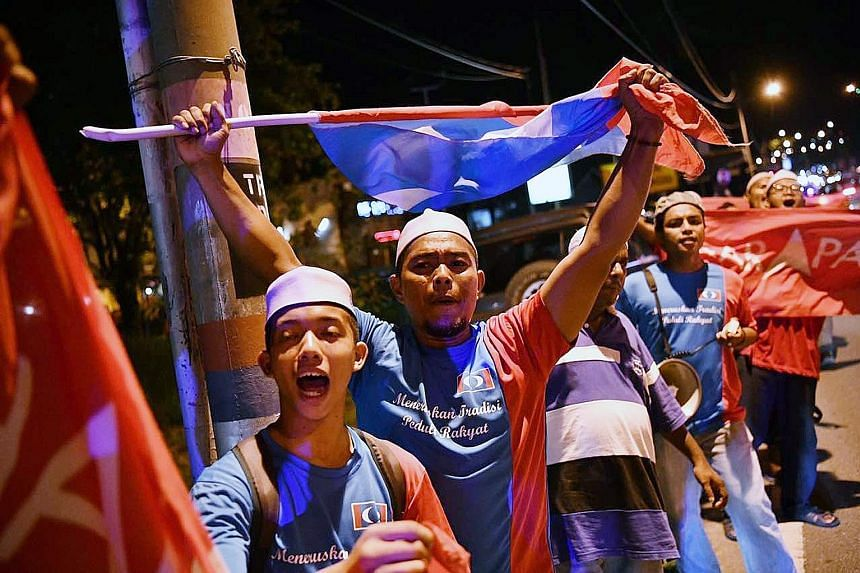 Jubilant Pakatan Harapan supporters celebrating Mr Anwar's win outside the official counting centre. The Election Commission said 58.2 per cent of the 68,317 eligible voters had cast their votes yesterday.