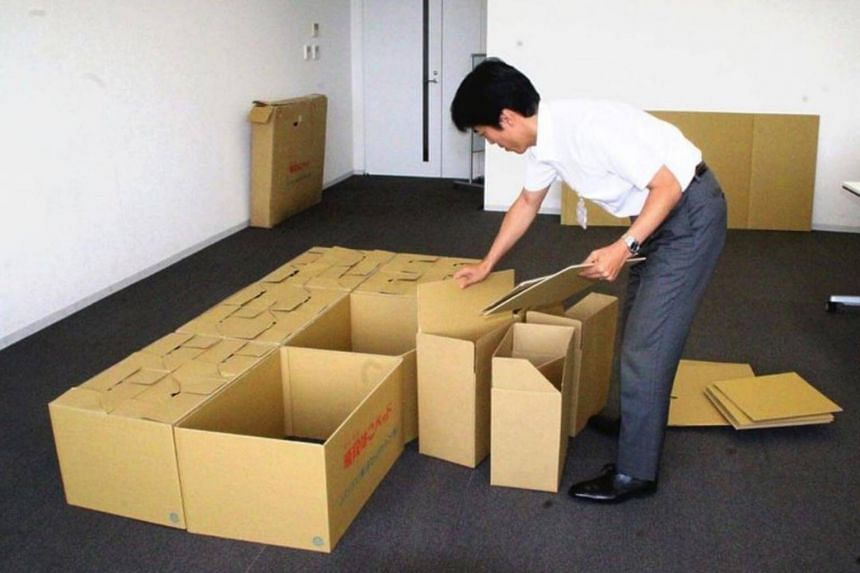 A cardboard bed is put together using small boxes at the Minami-Awaji city office in Hyogo Prefecture, Japan.