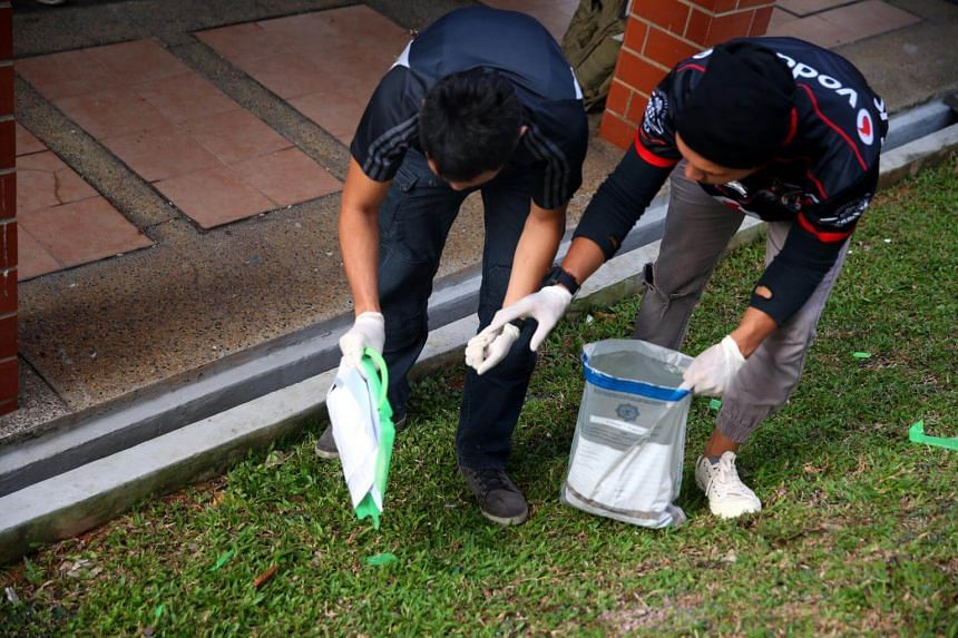 Two officers from the Special Task Force collecting suspected drugs and placing them into an evidence bag.