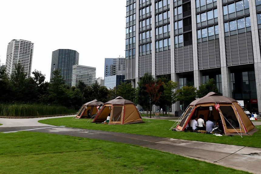 Company employees working inside camping tents erected on the lawn outside an office building in Tokyo, Japan, on Sept 11, 2018.