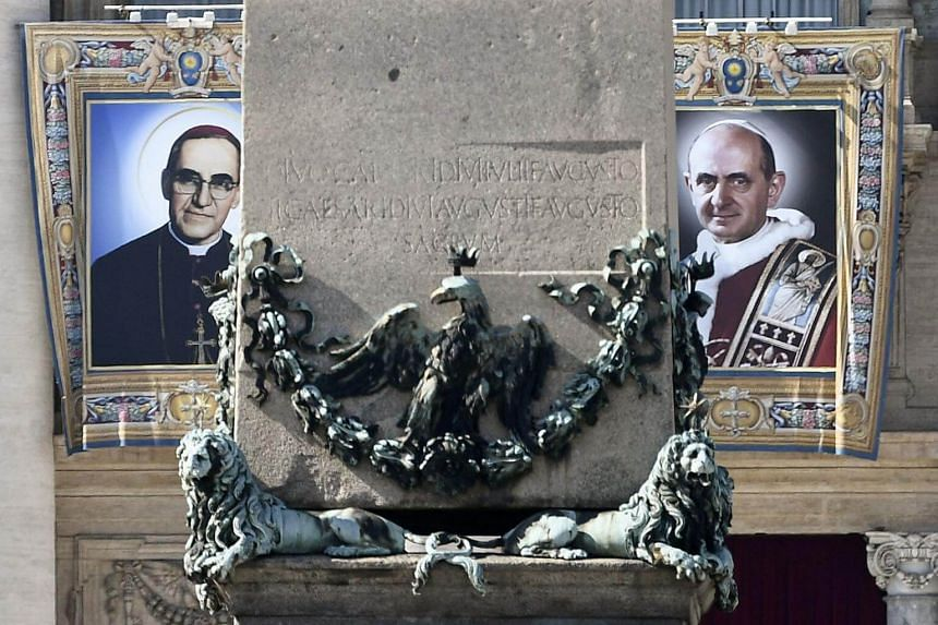 The tapestries of Roman Catholic Archbishop Oscar Romero (left) and Pope Paul VI hang from a balcony of the facade of St Peter's Basilica at the Vatican, on Oct 13, 2018.