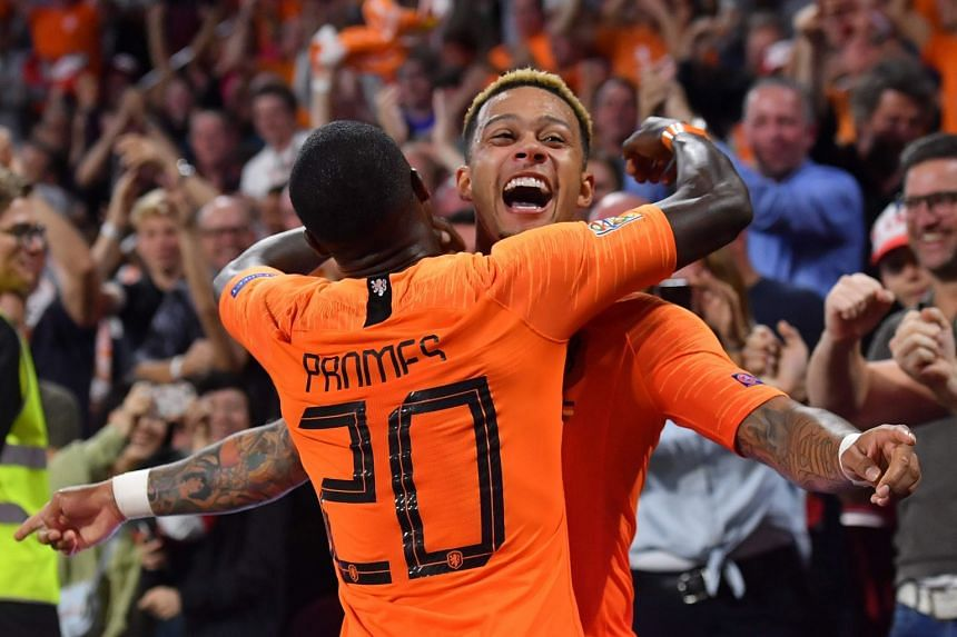 Netherlands' forward Memphis Depay is congratulated by team mates after scoring.