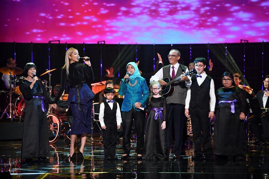 President Halimah Yacob (centre), performing with Mr Mohamed Abdullah Alhabshee (holding the guitar) and local songstress Aisyah Aziz at the President's Star Charity 2018.