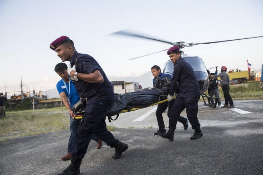 Nepalese trekking staff and policemen shift the dead bodies of climbers at the helipad of Teaching Hospital in Kathmandu, Nepal on Oct 14, 2018.