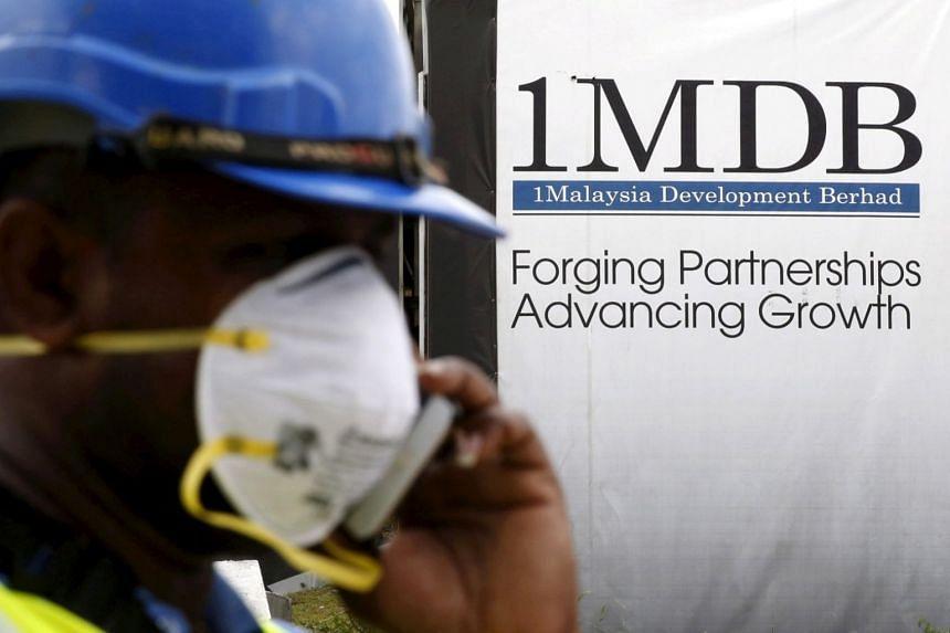 A construction worker talks on the phone in front of a 1MDB billboard at the Tun Razak Exchange development in Kuala Lumpur, Malaysia.
