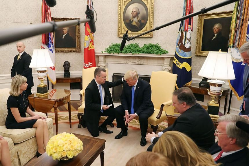 Pastor Andrew Brunson (left) and President Trump participate in a prayer in the Oval Office.